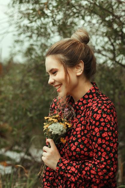 彼女の手で野生の花の花束を保持している赤い花のドレスでかわいい笑顔の女の子の肖像画。 Premium写真