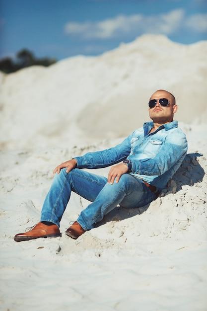 Парень сидит на песке, загорелая джинсовая одежда Premium Фотографии