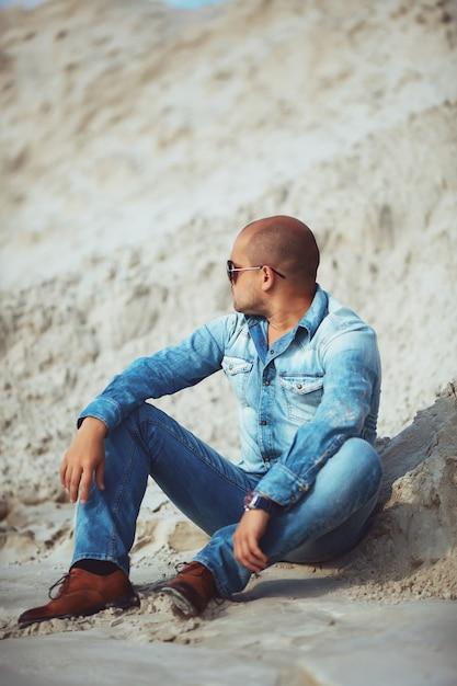 Человек сидит на песке в очках смотрит в сторону Premium Фотографии