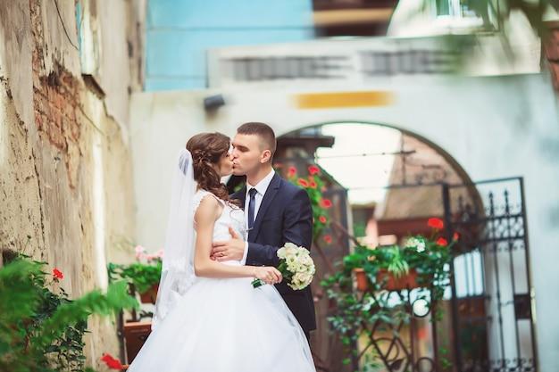 結婚式の写真撮影。街を歩いて新郎新婦。夫婦が抱き合ってお互いを見つめる。 Premium写真