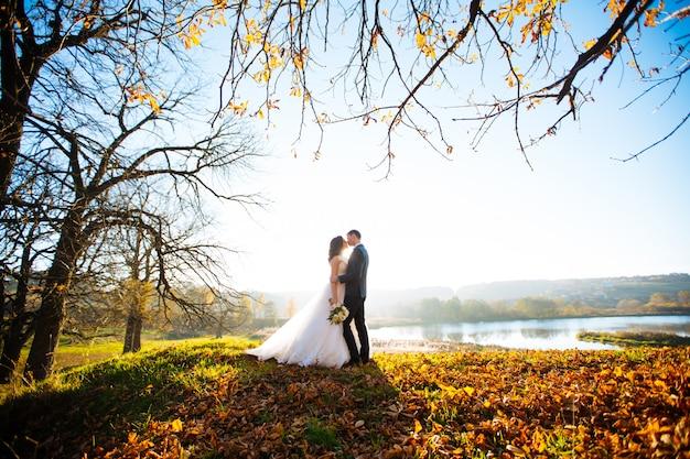 新婚夫婦は、屋外の散歩で結婚式の日にキスと笑顔します。花の花束と面白い花嫁。 Premium写真