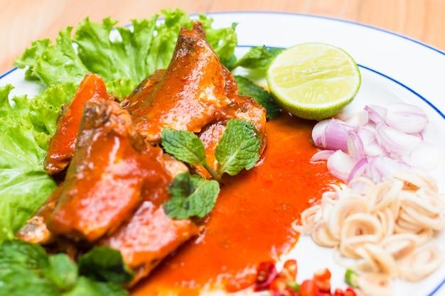 Рыба скумбрии в томатном соусе и повар в тайском остром салате. Premium Фотографии