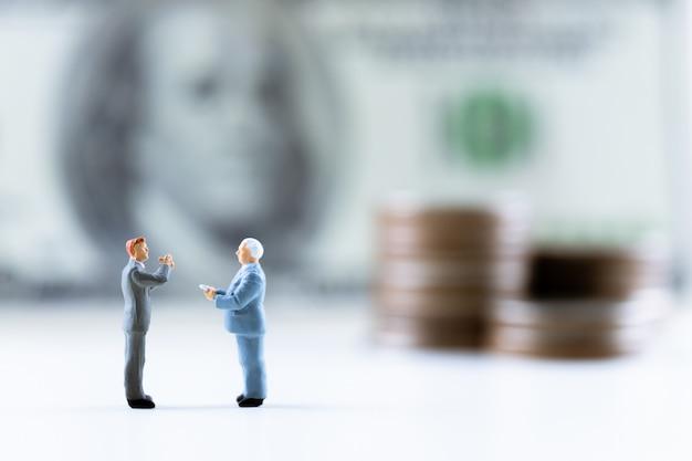 ミニチュアの人々、コインスタックとドル紙幣の上に立って実業家ステップアップバックグラウンド。 Premium写真