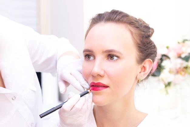 Молодая женщина, имея перманентный макияж на губах Premium Фотографии