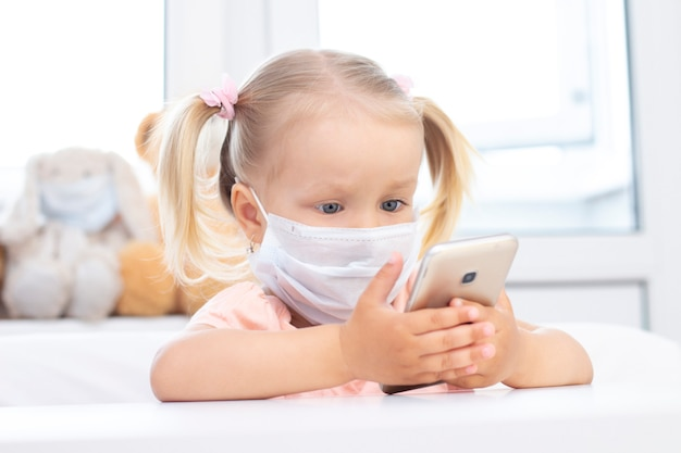 携帯電話を使用して防護マスクの女の子。 Premium写真