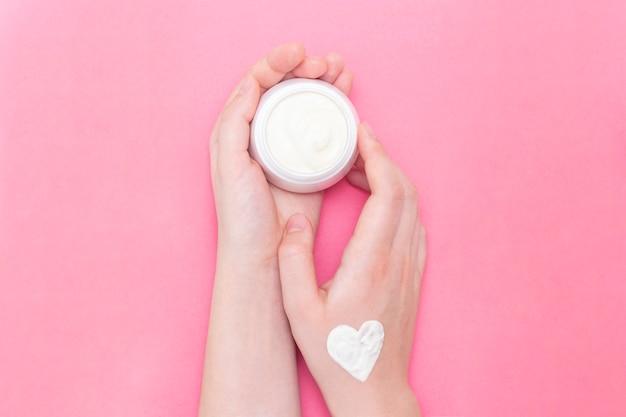 ピンクのクリームの瓶を持つ女性を手します。 Premium写真