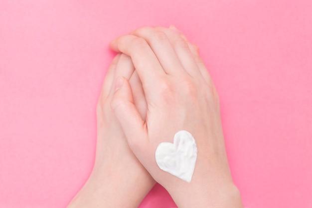 ピンクの手女性。冬の清潔でやわらかな肌のための保湿剤。 Premium写真