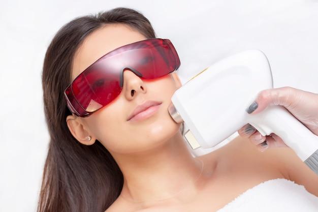 ビューティーサロンでの光脱毛の手順。ビューティーセンターで顔に脱毛レーザー治療を受ける若い女性をクローズアップ Premium写真