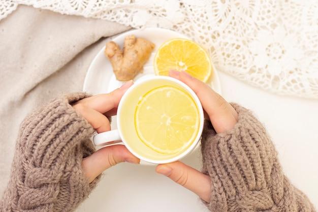 Руки женщины с чаем, лимоном, имбирем на белой предпосылке. плоская планировка концепция здоровья, иммунитета, народной медицины. Premium Фотографии
