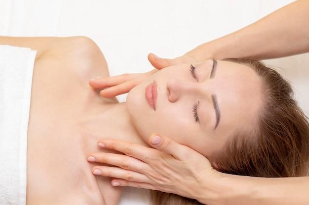 スパサロンでマッサージを楽しんでいる若い女性。フェイスマッサージ。ビューティースパサロンでスパマッサージ治療を得る若い女性のクローズアップ。スパの肌と体のケア。フェイシャルビューティートリートメント。 Premium写真