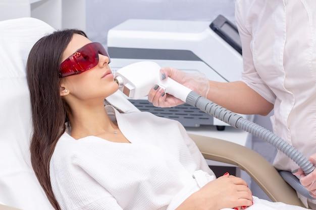 Процедура фотоэпиляции в салоне красоты. молодая женщина, получающая эпиляцию лазером на лице в салоне красоты крупным планом Premium Фотографии