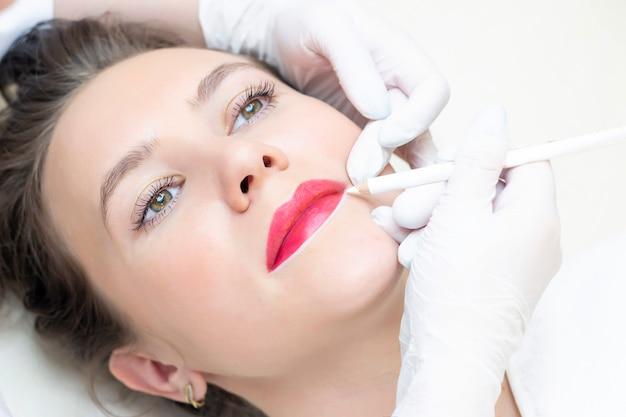 Молодая женщина, имея перманентный макияж на губах в салоне косметологов. перманентный макияж (тату). рисование контура белым карандашом для губ Premium Фотографии
