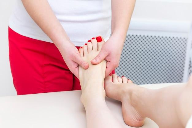 スパサロンで足裏マッサージ。フットマッサージは、スキンケアをリラックスします。治療用ペディキュア。 Premium写真
