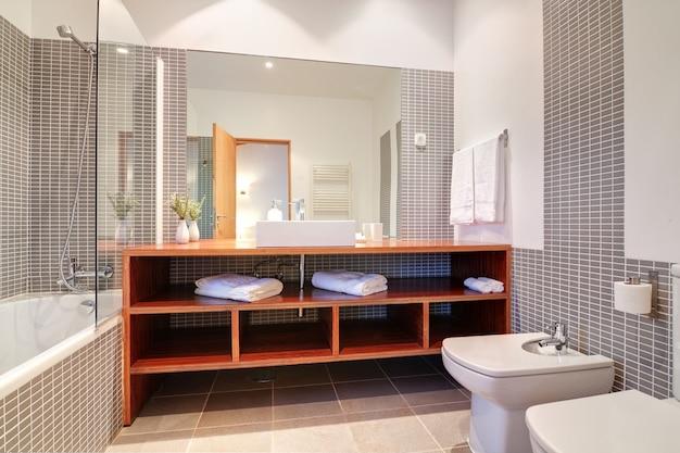 Ванная комната с раковиной, биде и полотенцами. Premium Фотографии