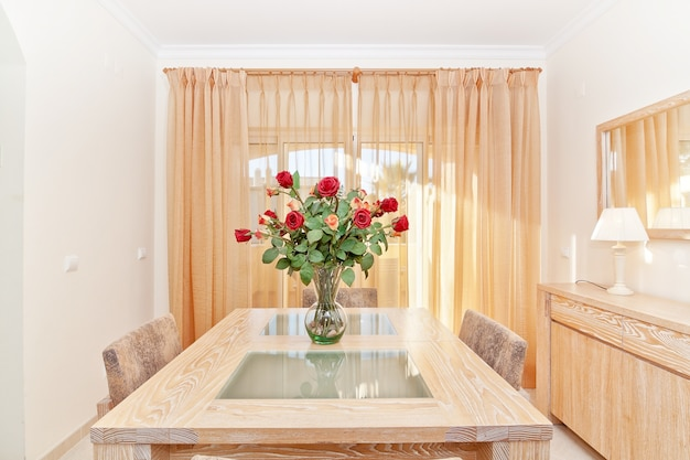 В гостиной красивый букет красных роз в вазе. на столе. Premium Фотографии
