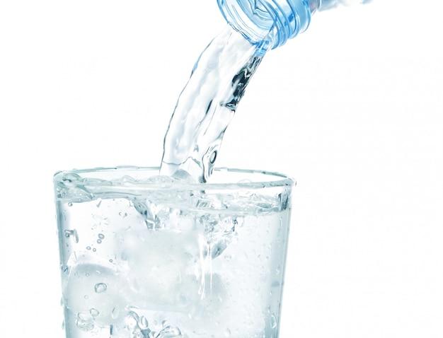 きれいな水が流れる氷の入ったグラスの中。白い壁の上。 Premium写真