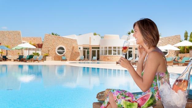 プールサイドでシャンパングラスを持つ少女。夏休み。 Premium写真