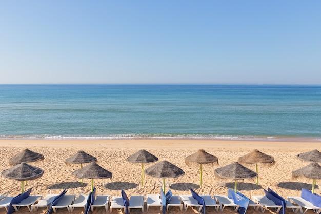 Экзотический пейзаж с зонтиками на пляже возле пляжа. в португалии. Premium Фотографии