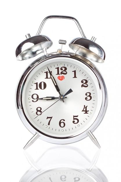 白い壁に銀の目覚まし時計。 Premium写真