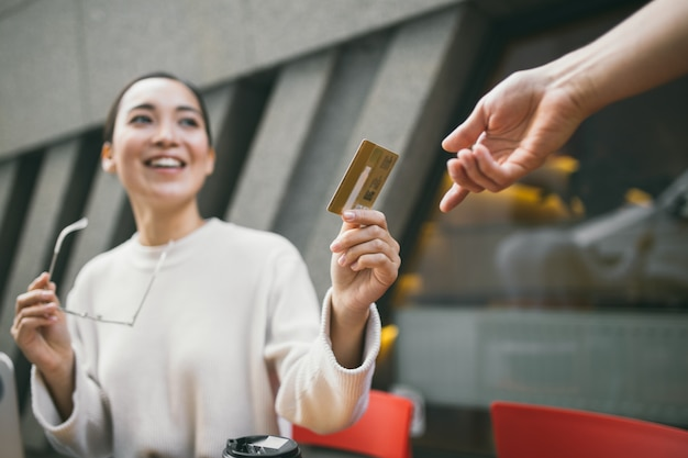 Молодая азиатская женщина с очками в руке сидит за пределами кафе, платить за кофе или чай и с помощью ноутбука Premium Фотографии