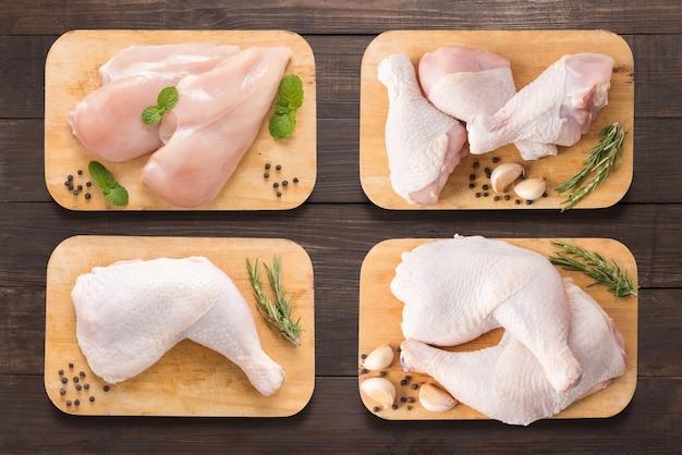 木製の背景にまな板の上に生の鶏肉を設定します。 Premium写真
