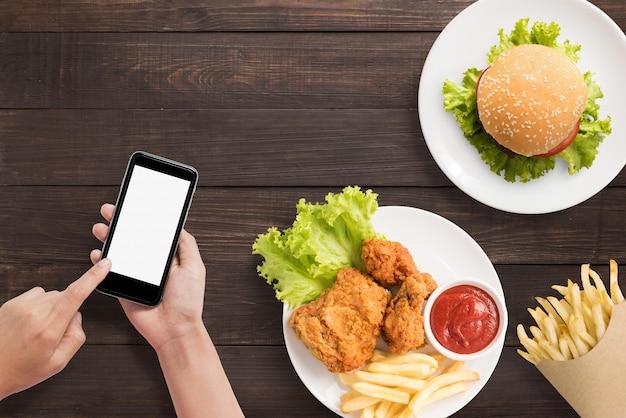 Используя смартфон с гамбургером, картофелем фри и жареной курицей на деревянных фоне Premium Фотографии