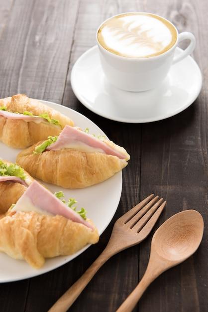 パルマ産ハムと木製のテーブルの上のコーヒーのクロワッサン Premium写真