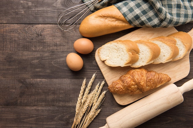 焼きたてのクロワッサン、バゲット、木製の背景に卵 Premium写真