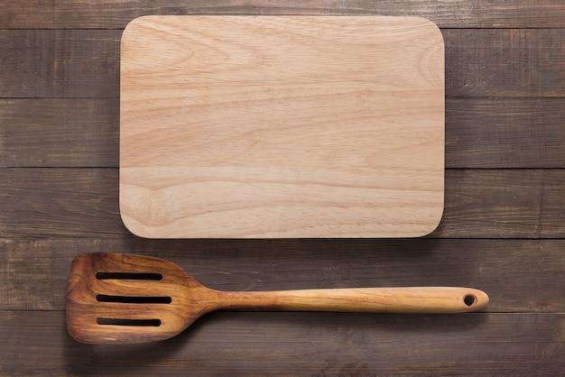 Разделочная доска и шпатель на деревянном фоне Premium Фотографии