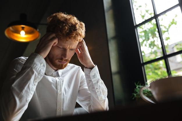 若い赤毛のクローズアップの肖像画を生やした白いシャツの過労の男がオフィスに座っている間彼の頭に触れる 無料写真