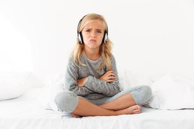 組んだ腕と足をベッドに座ってヘッドフォンで動揺の女性の子供、 無料写真