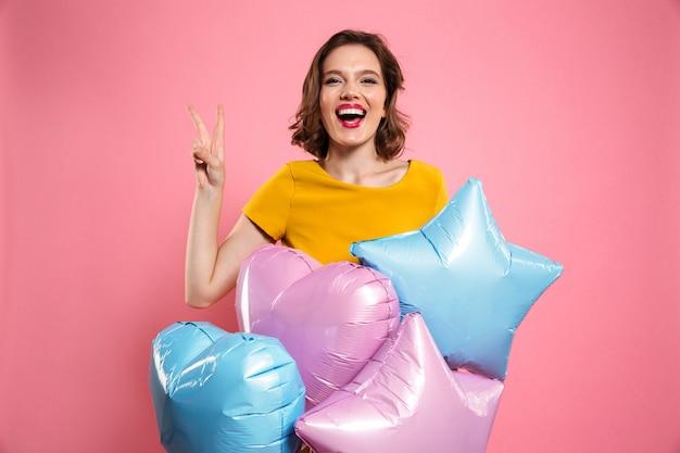 Крупным планом фото с днем рождения девушки с красными губами, держа воздушные шары, показывая жест мира, Бесплатные Фотографии