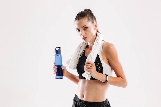 Уставшая потная фитнес женщина с полотенцем на шее Бесплатные Фотографии