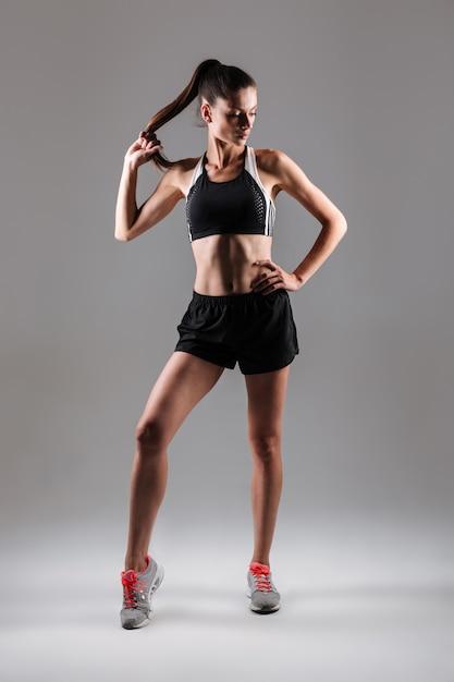 Портрет молодой стройной женщины фитнеса позирует стоя Бесплатные Фотографии