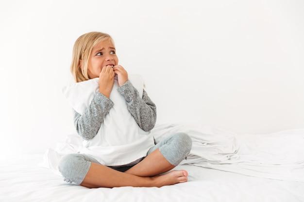 枕を抱いてパニックに陥った少女の肖像画 無料写真