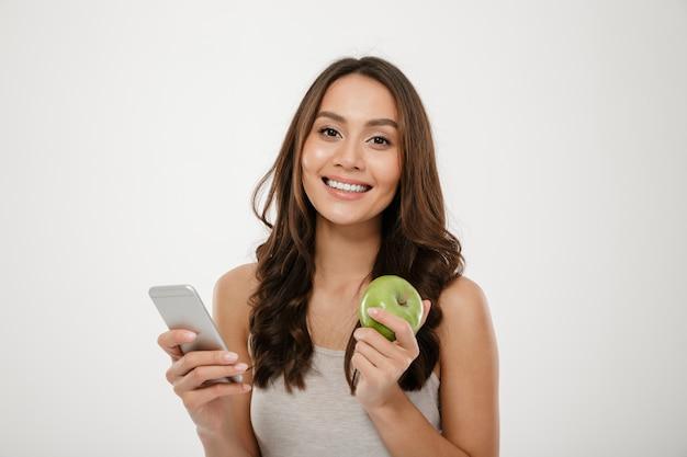 Портрет довольной женщины с идеальной улыбкой, используя серебряный смартфон и есть свежее зеленое яблоко, изолированное над белой стеной Бесплатные Фотографии