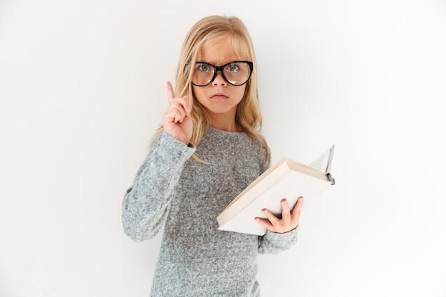 指で上向き、本を保持している大人のためのメガネで深刻な少女のクローズアップの肖像画 無料写真