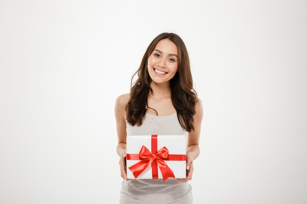 Фотография довольной женщины, держащей подарочную коробку с красным бантом, возбужденного и удивленного, чтобы получить подарок на день рождения, изолированного над белым Бесплатные Фотографии