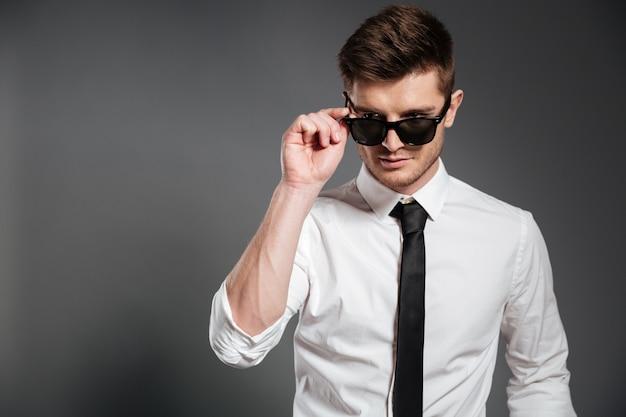 白いシャツに立っているとサングラスでポーズでハンサムな男 無料写真