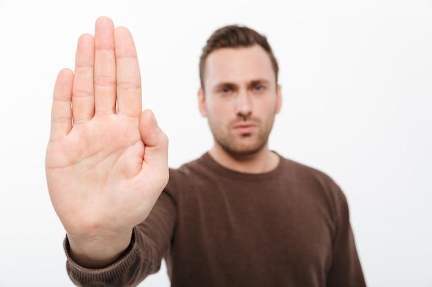 Красивый молодой серьезный человек, показаны стоп жест. Бесплатные Фотографии
