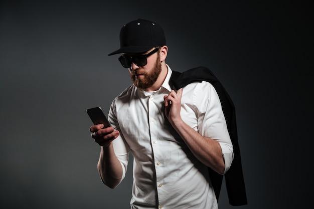 Человек в солнечных очках и рубашке держа телефон и смотря прочь Бесплатные Фотографии