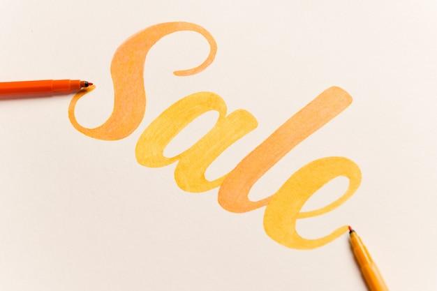 オレンジ塗装の白い背景の上の販売をレタリング 無料写真