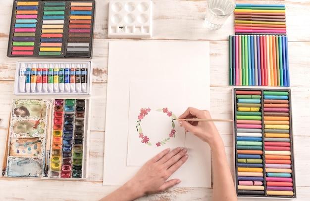 Молодой художник рисует цветочный узор акварельной краской и кистью на рабочем месте Бесплатные Фотографии