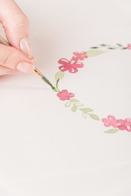 Молодой художник рисует цветочный узор акварельной краской и кистью на бумаге на рабочем месте Бесплатные Фотографии