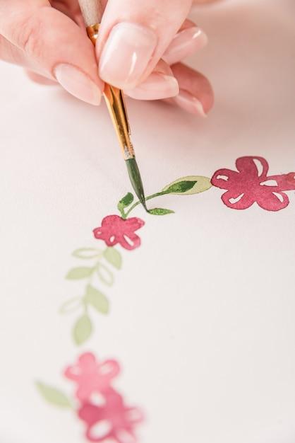 水彩絵の具とブラシで職場で紙の上に花のパターンを描く若いアーティスト 無料写真