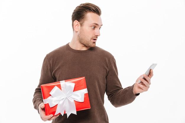 Шокирован молодой человек, держащий подарочной коробке сюрприз Бесплатные Фотографии