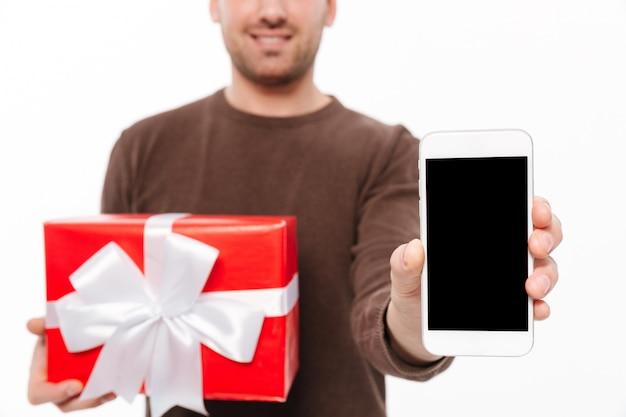 Улыбающийся молодой человек с подарочной коробкой Бесплатные Фотографии