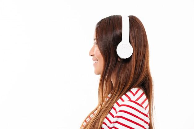 ヘッドフォンで若いアジアの女の子の側面図 無料写真