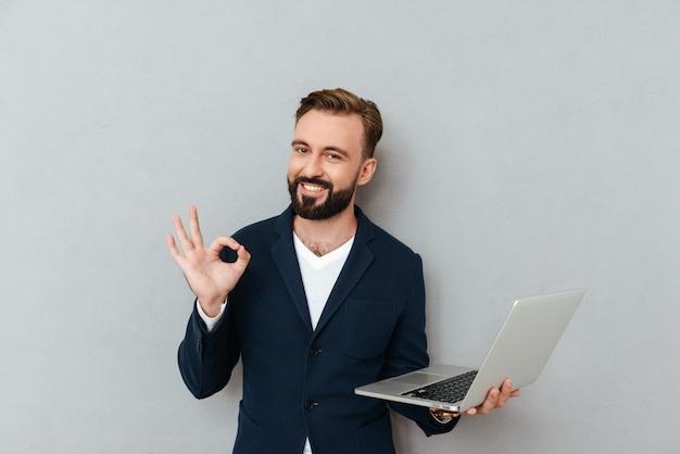 分離されたラップトップコンピューターを押しながらカメラを探しているスーツの若いひげを生やした男 無料写真