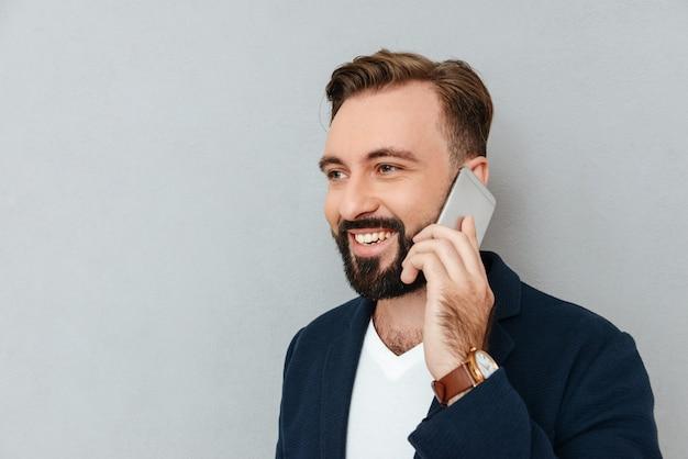 分離されたスマートフォンで話しているハンサムな男の肖像 無料写真
